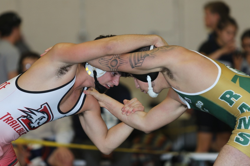 Colton Economy goes head to head at the beginning of a match at the Colorado State University Invitational. Courtesy of Wayne Briggs.