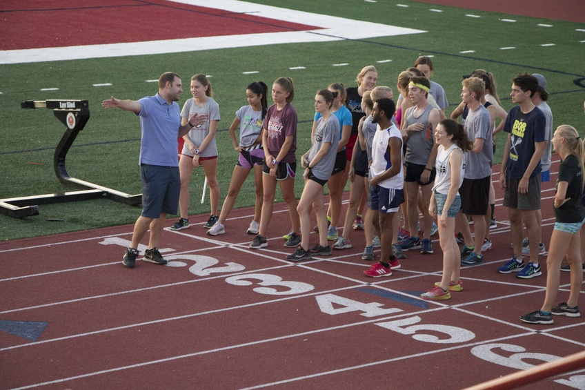 Coach Justin Decker gives the team instructions during practice. Cross country and track had to start practice later in the season due to the tracks recent renovations. Photo by Adriana Hymas.