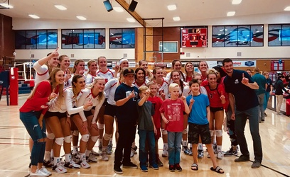 Volleyball groups together with family and assistant coach, after winning Senior Day match against Azusa Pacific University. DSU led the match, 1-0 in the first period.  Photo by Alexis McClain.