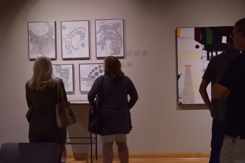Students and community members take time to peruse the art hung on every wall of the Sears Gallery on September 29. Photo by Camden Bennett.