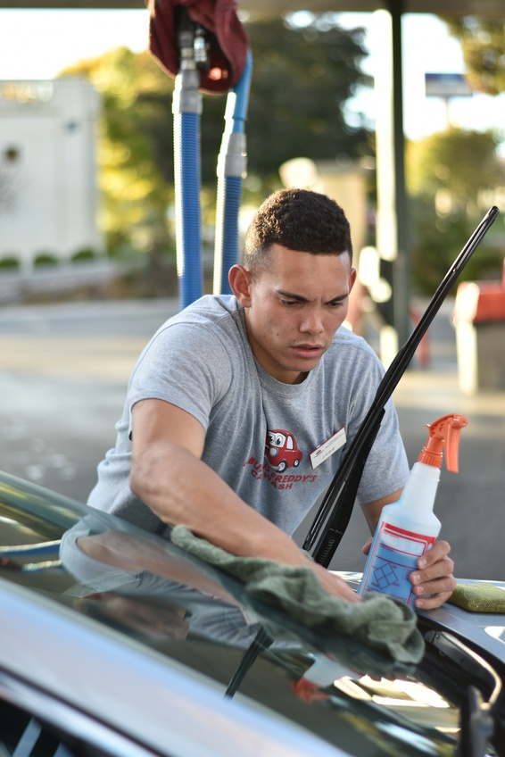 Josh Cook, a senior integrated studies major from Las Vegas, shines a windshield at Fabulous Freddy's Carwash. Photo by Kylea Custer.