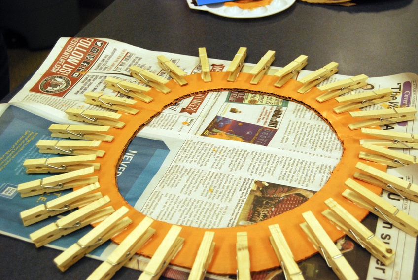 Step 3: Once the paint is dry, glue clothespins around the outer edge of the circle, leaving only a small space between them.