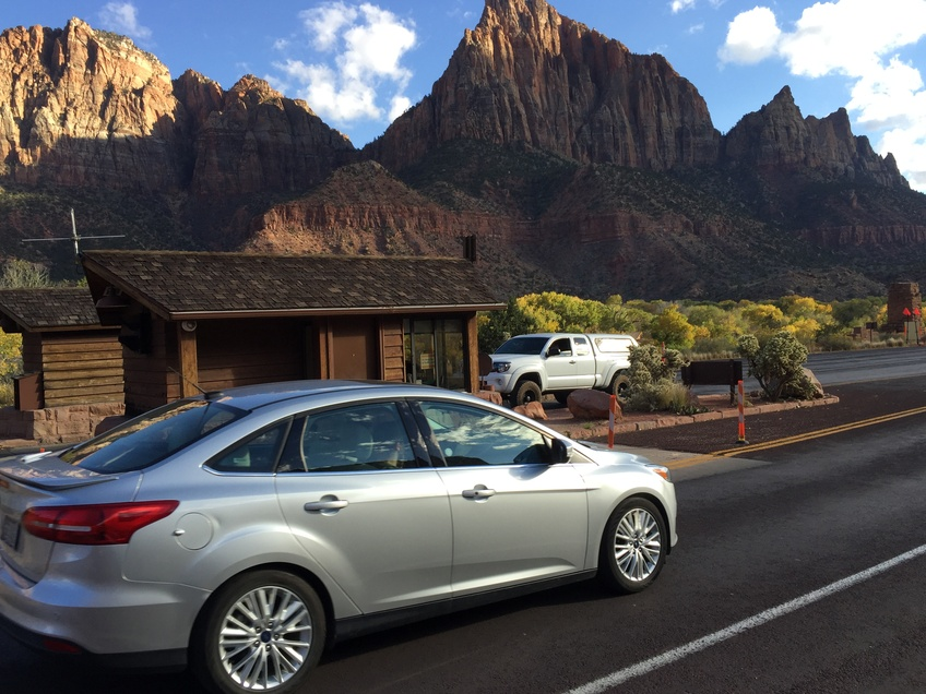 A car drives into the entrance of Zion National Park and pays $30 for a one-day pass. Photo by Trey Davis.