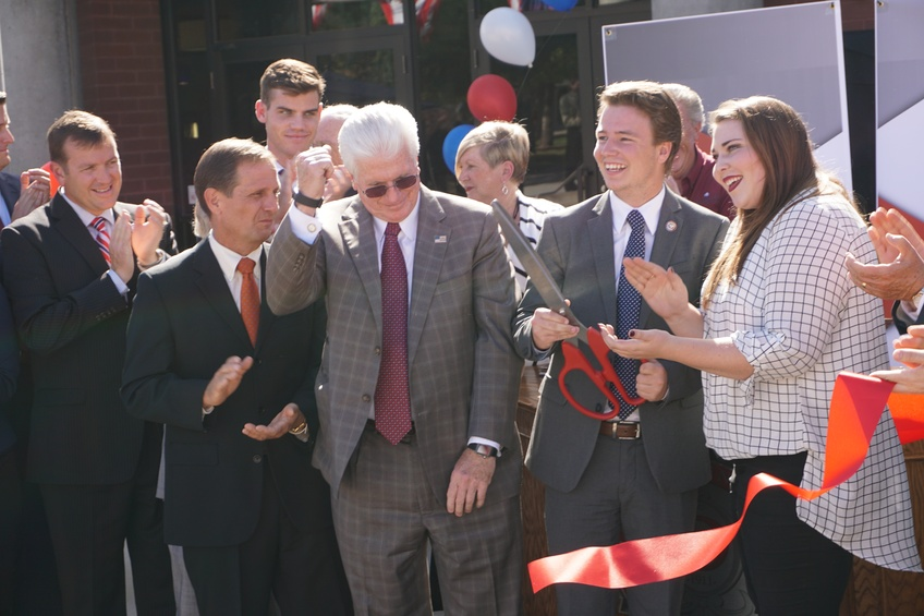 James Kener, a senior English major from Murray and student director of the DSU Institute of Politics, celebrates after cutting the ribbon at the grand opening of the IOP Wednesday.