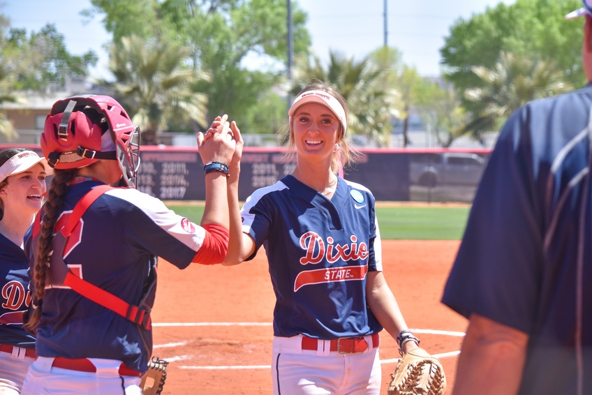 Hazel high-fives her teammate junior catcher Jessica Gonzalez, a business administration major from Kingsburg, California, after a strike out to end the top half of the inning.