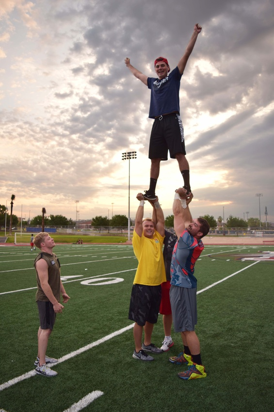 The men on the Dixie State University cheer team create a pyramid while practicing stunts and flips for their next performance at the Legend Solar Stadium. Photo by Camden Bennett.