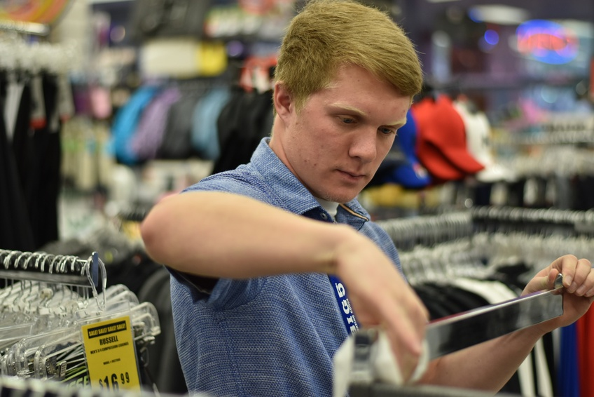 Brady Knight, a freshman biology major from Toole, cleans a clothing rack at Big 5 Sporting Goods on Red Cliffs Drive. Photo by Kylea Custer.