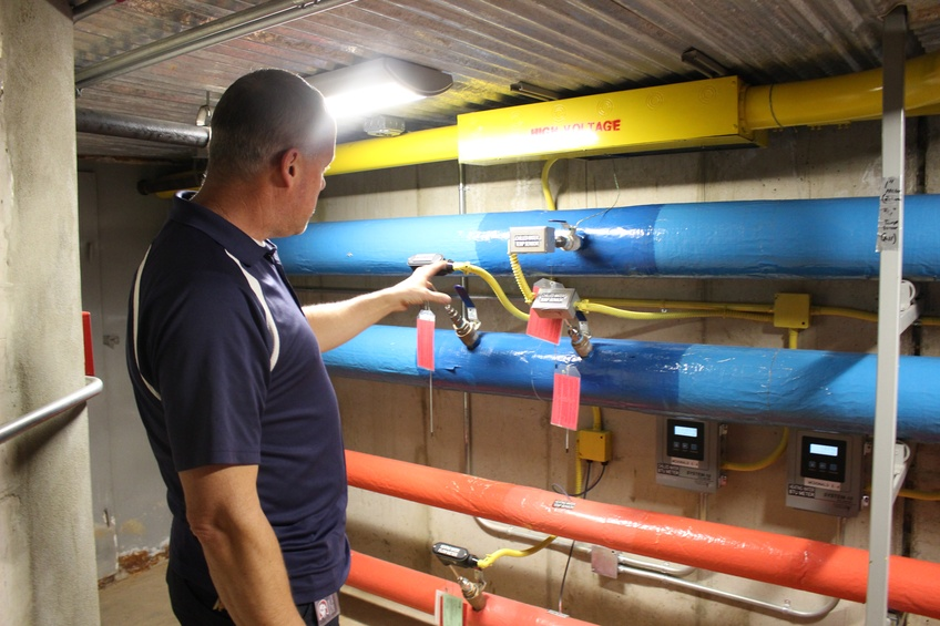 Bart Peacock, director of facility operations and energy, explains what the color codes on the pipes running through the tunnels under Dixie State University mean.