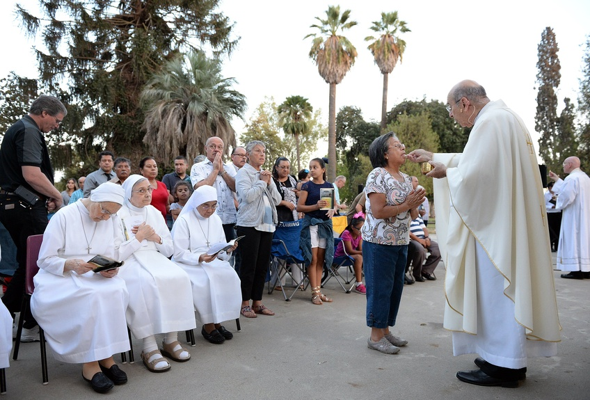 Bishop Armando X. Ochoa of the Roman Catholic Diocese of Fresno, Calif., gives communion to participants during a mass at Kearney Park as part of the Roman Catholic Diocese of Fresno's 50th anniversar