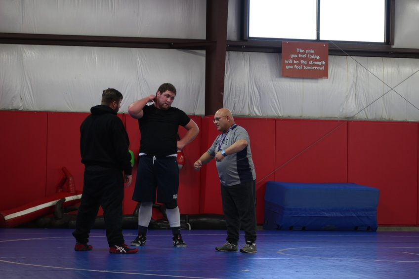 Wrestling Head Coach Wayne Briggs instructs his players on a move to improve their pin.