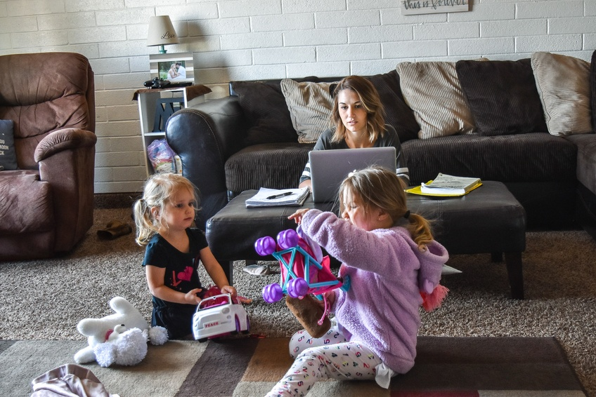 Averie Turpin, a senior communications major from West Jordan, tries to study at home while her kids play. Photo by Kylea Custer.